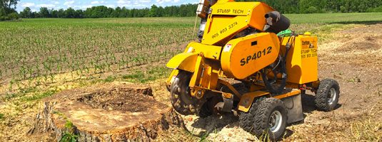 a stump grinder in the process of removing a stump, a corn field is visible in the background and blue sky with a few clouds