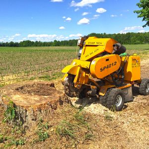 a large tree stump is being removed by a stump grinder, field crops are visible in the background
